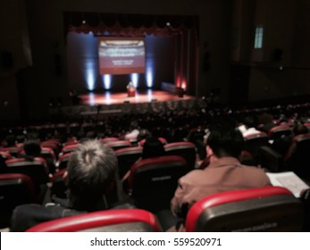 Audience meeting community in seminar hall with ted talk show blur image use for background. Ted talk show on stage of theatre concept.