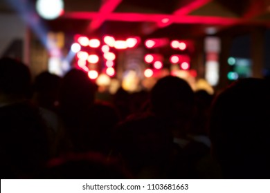 Audience at a music festival and lights streaming from the stage. Soft focus, blurred movement.