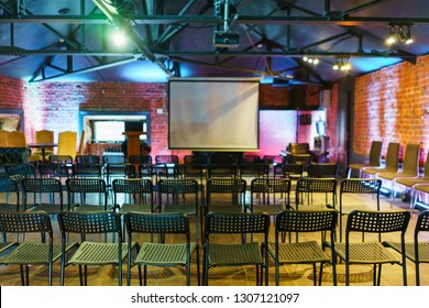 Audience, presentation, equipment. Loft room prepared for the speaker, a screen for the projector and slideshow, rows of seats. Training and presentation, courses for students. Soft focus.