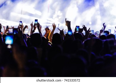 Audience recording video of band on mobile phone in concert.