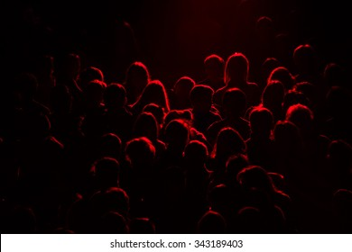 audience silhouette on purple and red light