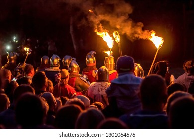 Audience silhouettes watch the flames at the forefront