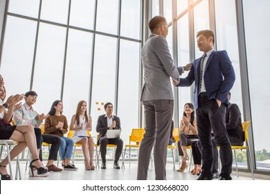 Audiences sitting and listening the speacker Shake hands with exclusive on the stage at meeting room, event and seminar concept