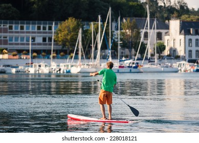AUDIERNE, FRANCE - AUGUST 12, 2014: Man rowing in the harbor. Audierne lies on a peninsula at the mouth of the Goyen river and for centuries was a fishing village.