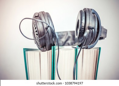 Audio book concept. Headphones and old book