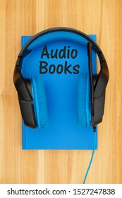 Audio books message with blue and black headset with microphone with a book on a wood desk