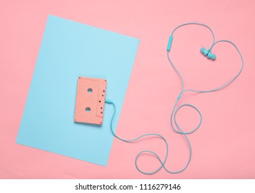 Audio cassette and earphones on a blue pink pastel background. Musical love concept. Retro style. Minimalism. Top View