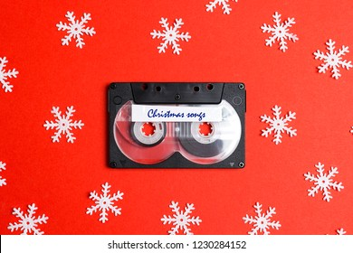 Audio cassette tape with decorative snowflakes on a red background. Music for Christmas mood. Nostalgia concept.