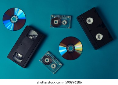 Audio cassettes, cassettes videos, CDs on a blue background. The evolution of media. Flat lay.Media 90s.