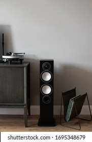 audio column with vinyl turntable and record stand on a grey wall background