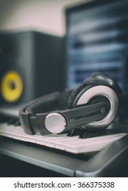 Audio earphones. Home recording studio with professional monitors and midi keyboard.