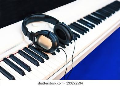 audio earphones on piano keyboards.