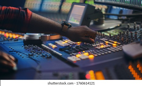 Audio Engineer, Music Creator, Musician, Artist Works in the Music Record Studio, Uses Surface Control Desk Equalizer Mixer. Buttons, Faders, Sliders to Broadcast, Record, Play Hit Song.