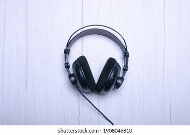 Audio headphones sound on wooden background. Top view with copy space
