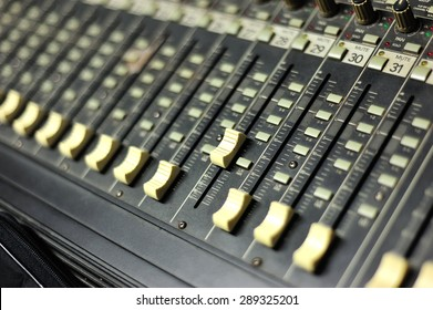 An Audio mixing table in soft light .