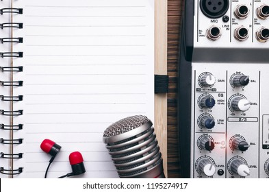 Audio recording studio concept. Karaoke. Song lyrics. Microphone, audio sound mixer, blank page notepad and headphones on the table.