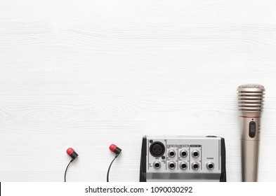 Audio recording studio desk table. Karaoke mock up. Song lyrics. Microphone, sound mixer and headphones on white wooden table background with copy space.