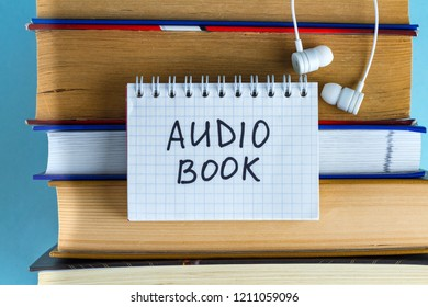 Audiobook concept. Headphones and books on a blue background. Listening audiobooks without looking up from work.