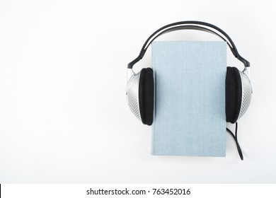 Audiobook on white background. Headphones put over blue hardback book, empty cover, copy space for ad text. Distance education, e-learning concept