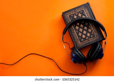 Audiobook, podcast and listening to literature concept with headphone on a vintage book on colorful orange background with copy space