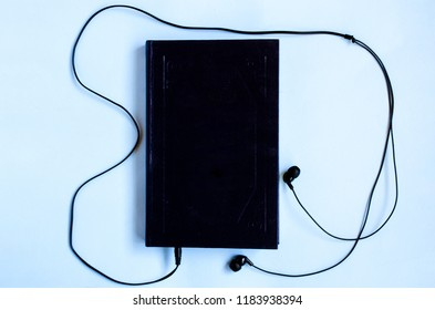 Audiobooks concept. The book with headphones connected