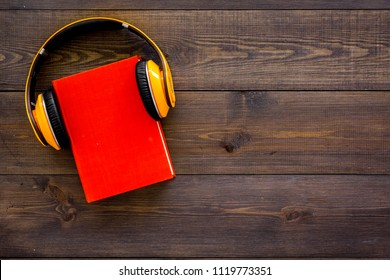 Audiobooks concept. Headphones put over hardback book with empty cover on dark wooden background top view copy space