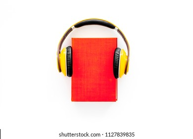 Audiobooks concept. Headphones put over hardback book with empty cover on white background top view copy space