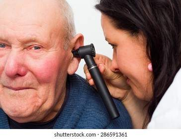 Audiologist checking elderly man's hearing with audioscope.