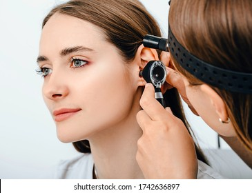 Audiologist doctor doing an ear exam with an otoscope to a patient woman. Audiology. Hearing test