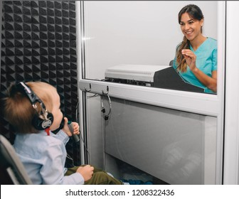 audiologist doing hearing exam to a little boy using audiometer in special audio room.