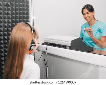 audiologist doing hearing exam to a little girl using audiometer in special audio room.