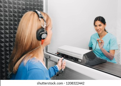 audiologist doing hearing exam to a mature patient using audiometer in special audio room.
