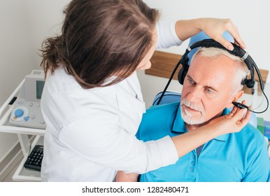 audiologist doing hearing test to a mature man at hearing clinic