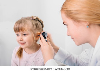 audiologist examining little patient with otoscope, hearing exam of child