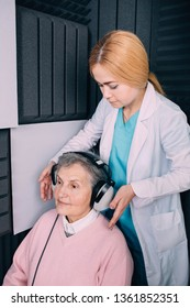 Audiologist placing a headset on senior patient for audiometric test