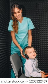 audiologist prepares little boy to hearing exam using headphones in special audio room.
