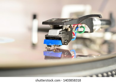 Audiophile cartridge mounted in shell with reflection in mirror surface. Vinyl records equipment, macro, close-up