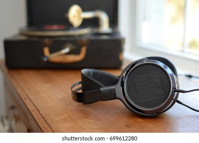 Audiophile Headphones with portable vintage Gramophone Victrola record player. Old and new technology.