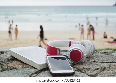Audiophile Headphones with smart phone on beach background Concept relax on vacation time in summer