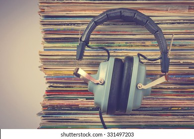 Audiophile headphones and a stack of old vinyl records.Stylized old color photo.