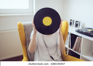 Audiophile holding vinyl record in front of head. Love music, audiophile, vinyl, music records