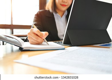 Audit business woman working with notebook and tablet on desk.