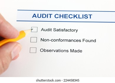Audit checklist and human hand with pencil.