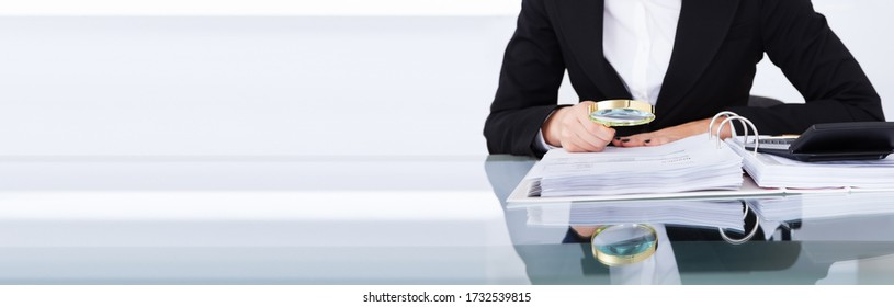 Auditor Doing Financial Audit And Tax Fraud Inspection Using Magnifying Glass