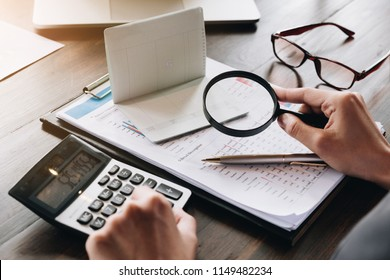 An auditor hand holding magnifying glass over saving account passbook for looking and analysis financial data,  Business finances and Saving concept.