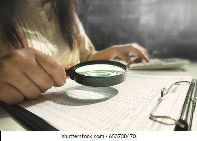 Auditor or internal revenue service staff, Business women using magnifying for checking annual financial statements of company. Audit Concept.
