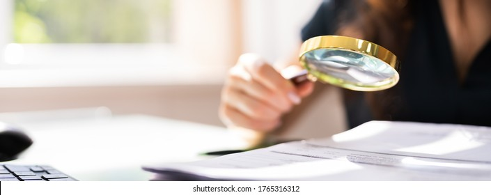 Auditor Investigating Corporate Fraud Using Magnifying Glass