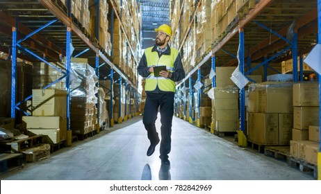 Auditor Wearing Hard Hat with Tablet Computer Counts Merchandise in Warehouse. He Walks Through Rows of Storage Racks with Merchandise.