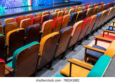 The auditorium in the theater. Multicolored spectator chairs. The stage with scenery and curtains.
