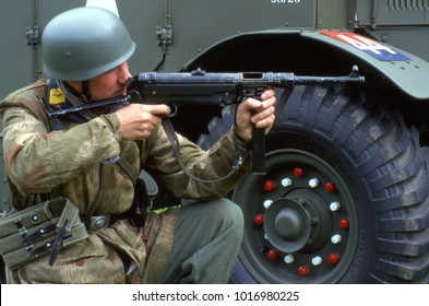 Audley End House Essex June 1995. A WW2 German reenactor wearing the uniform of a German Paratrooper crouches next to an English Bedford truck firing his MP40 machine gun.
